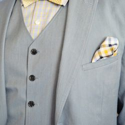 The groom wears a Goodale suit and a Michael Kors shirt. The pocket square and bow tie are from Hilfiger.
