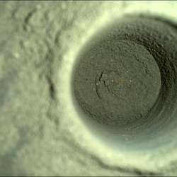 A closeup of the hole left by Perseverance, captured by the rover's SHERLOC WATSON camera.