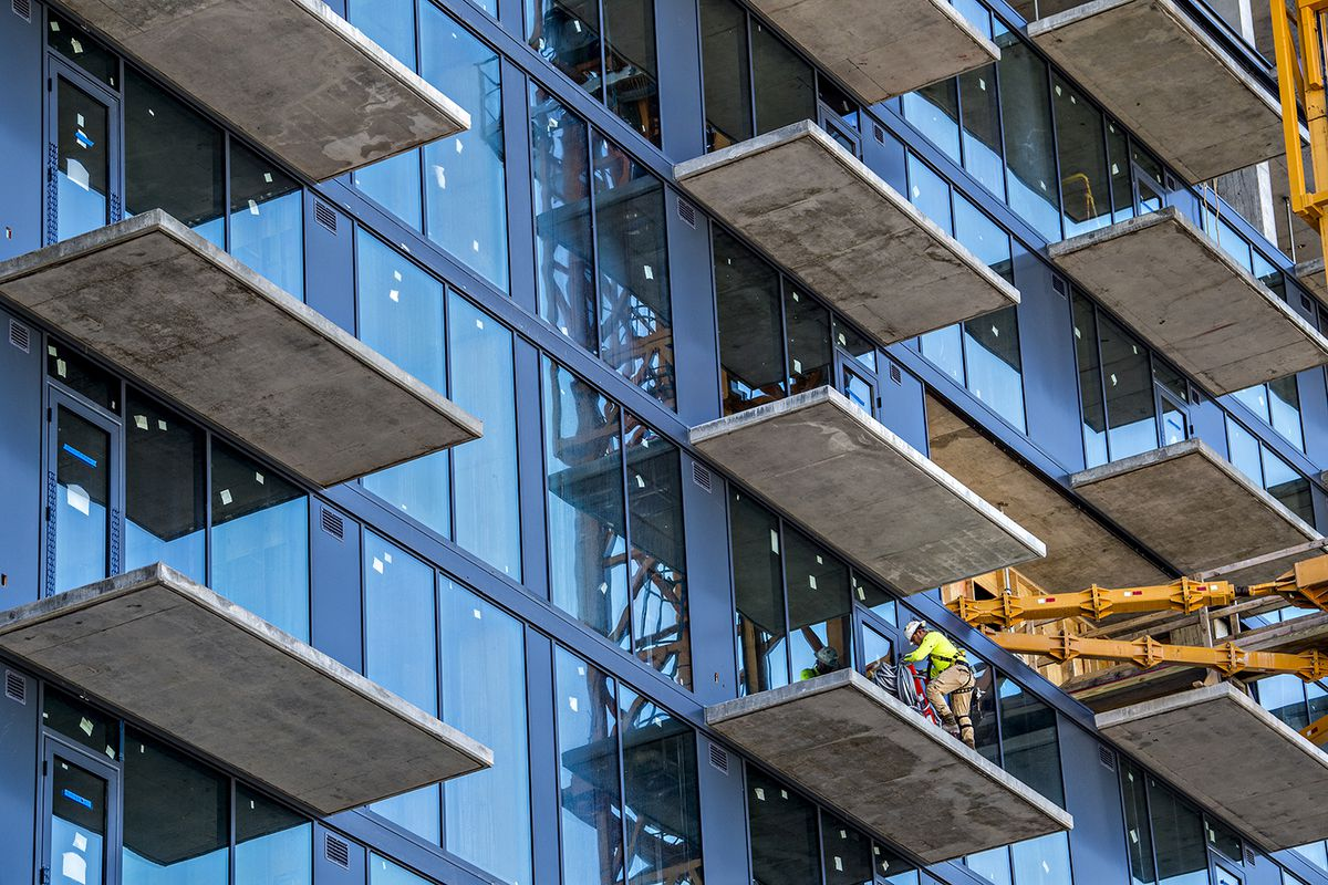 A worker on a high glassy tower working on the patio.