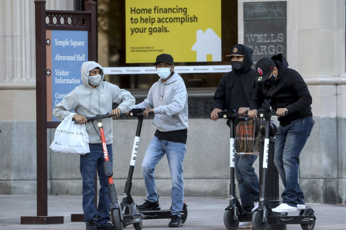 E-scooter riders wear masks in downtown Salt Lake City.