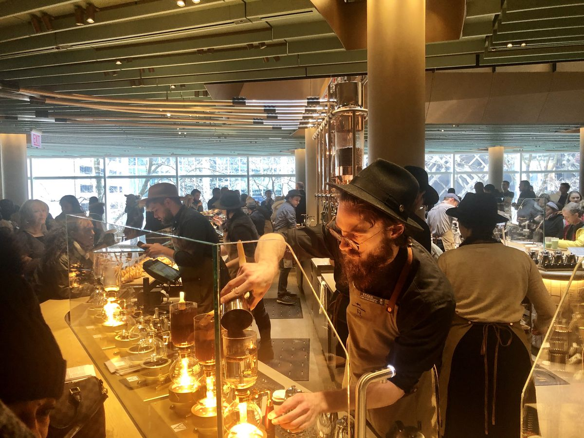 A view of a white bearded man with a hat making coffee behind a glass shield for a large crowd of customers.