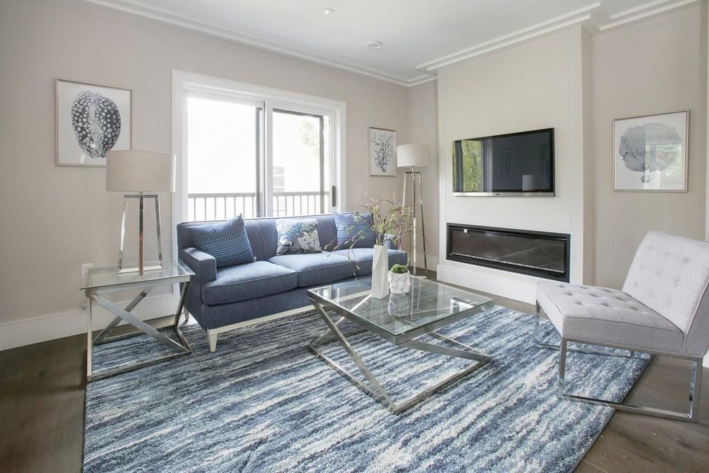 A living room with a couch and other furniture in front of a narrow electric fireplace.