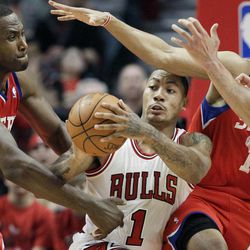 Chicago Bulls guard Derrick Rose (1) looks to a pass away from Philadelphia 76ers forward Elton Brand (42) and guard Evan Turner (12) during the second quarter of Game 1 in the first round of the NBA basketball playoffs in Chicago, Saturday, April 28, 2012.