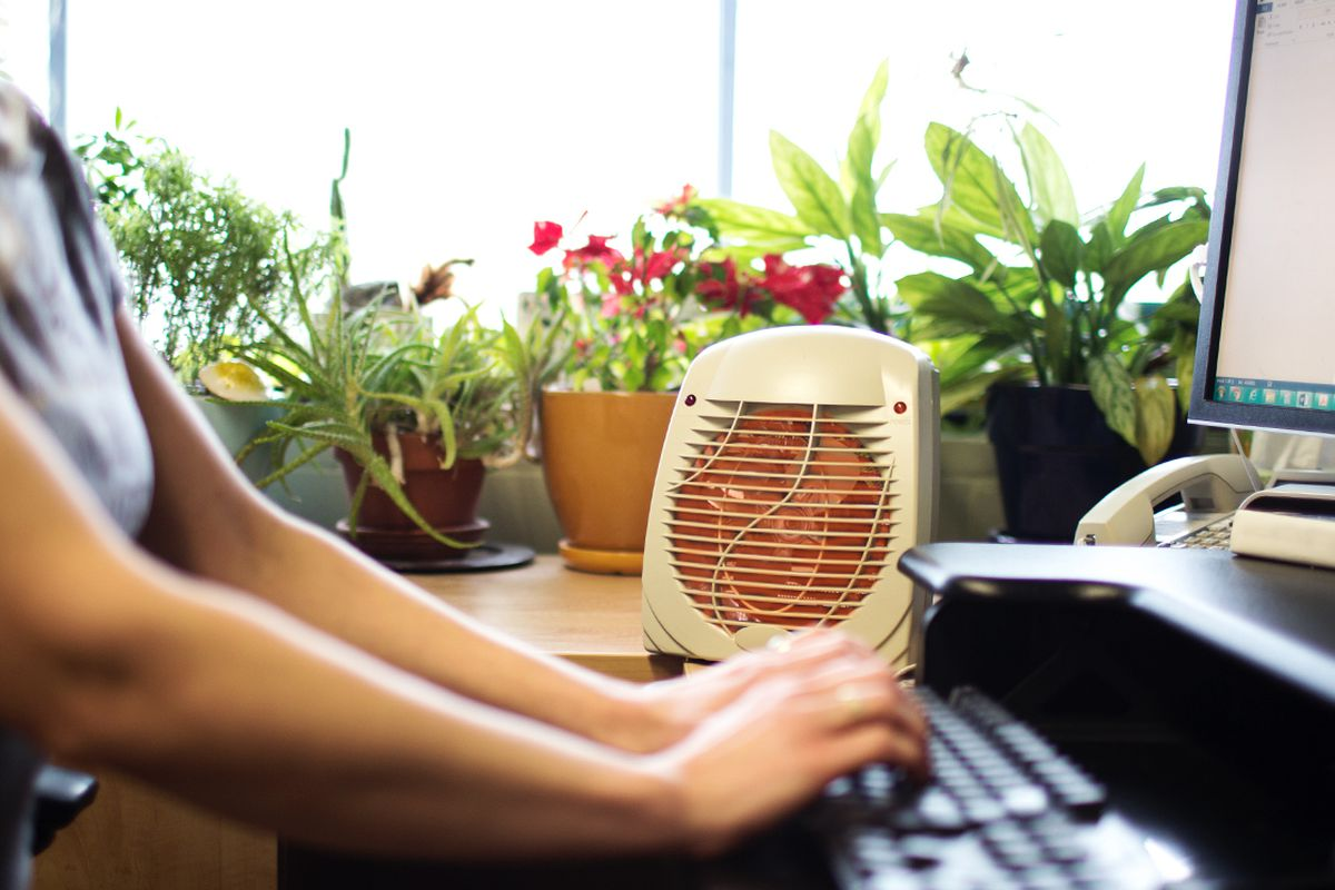 Worker at desk with space heater