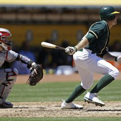 Oakland Athletics' Jaycob Brugman hits a single off Cleveland Indians' Trevor Bauer in a game Sunday, July 16, 2017, in Oakland, Calif. Brugman played college baseball at BYU.