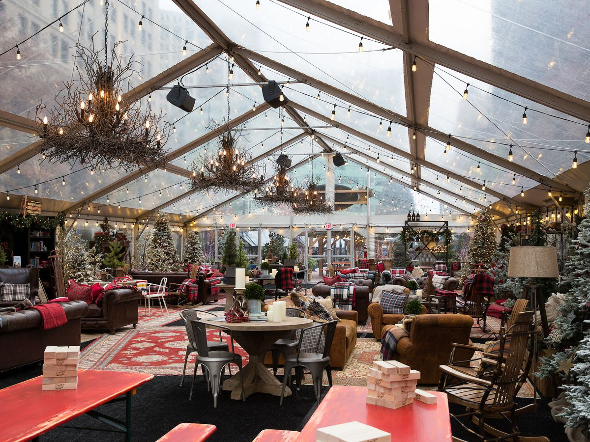 A large covered space filled with chairs, tables, Christmas trees, and other holiday trinkets.