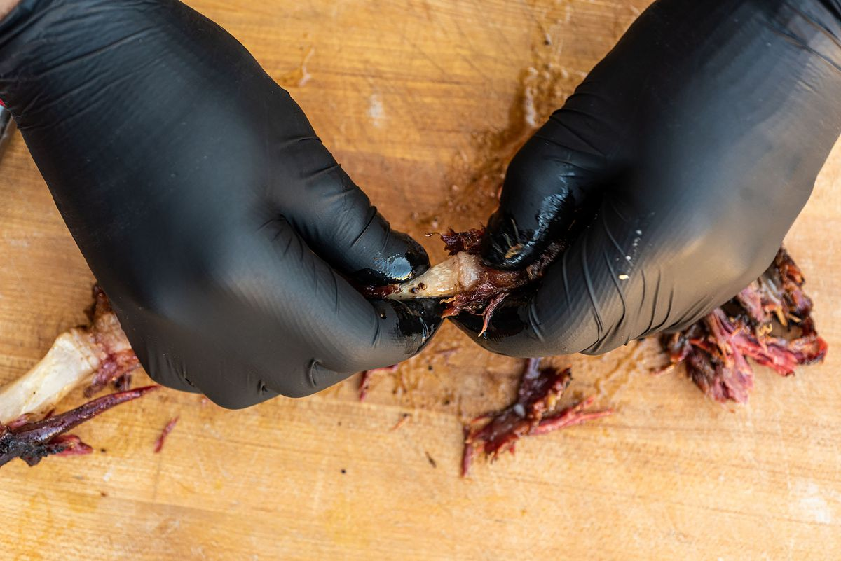 Pulling meat off the tail bone for oxtail.