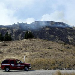 A fire vehicle drives past a hillside left scorched from flames the night before at one end a wildfire Monday, Sept. 10, 2012, near Wenatchee, Wash. Crews in central Washington and Wyoming worked Monday to protect homes from two of the many wildfires burning throughout the West as a destructive fire season stretches into September with no relief expected from the weather anytime soon. The National Weather service issued red-flag warnings for wide swaths of eastern Washington and Oregon, Idaho, Montana and all of Wyoming, meaning conditions could exacerbate blazes.