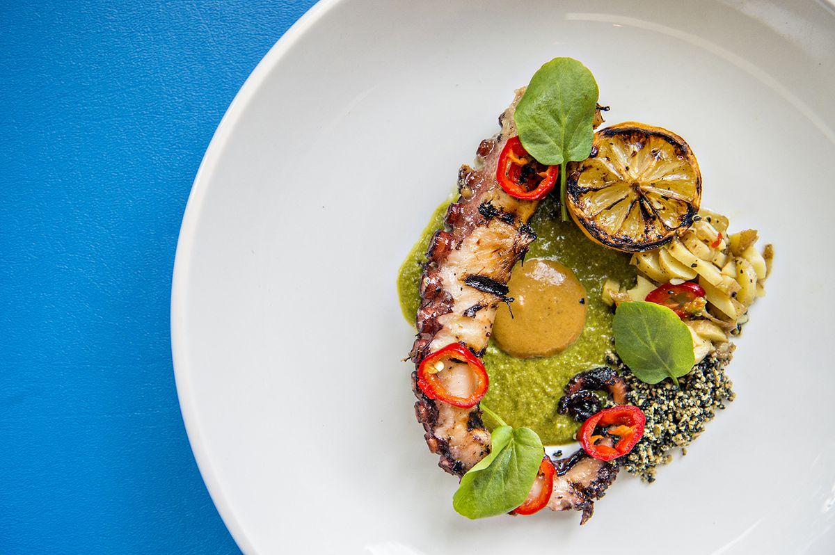 The charred octopus with pipian, salsa semilla, chipotle aioli, and potatoes at Lola Coastal Mexican