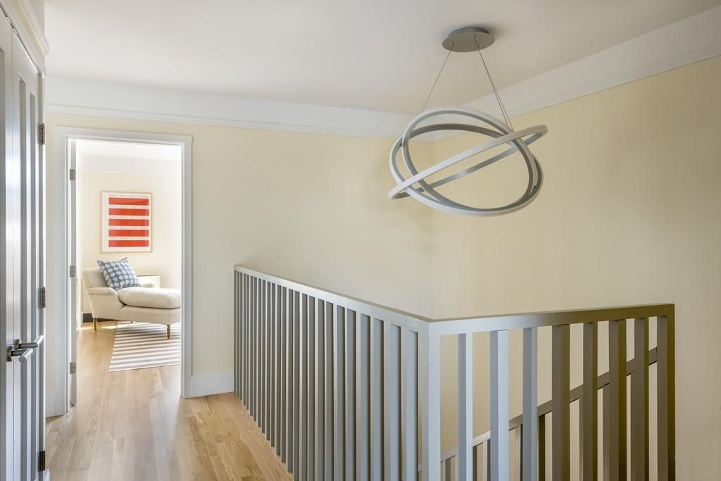 The top of that staircase and a hallway, with an elliptical sculpture hanging above it all.