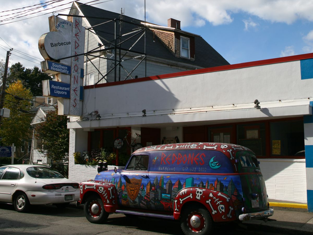 A red car covered with Redbones-themed art is parked outside of Redbones in Somerville.