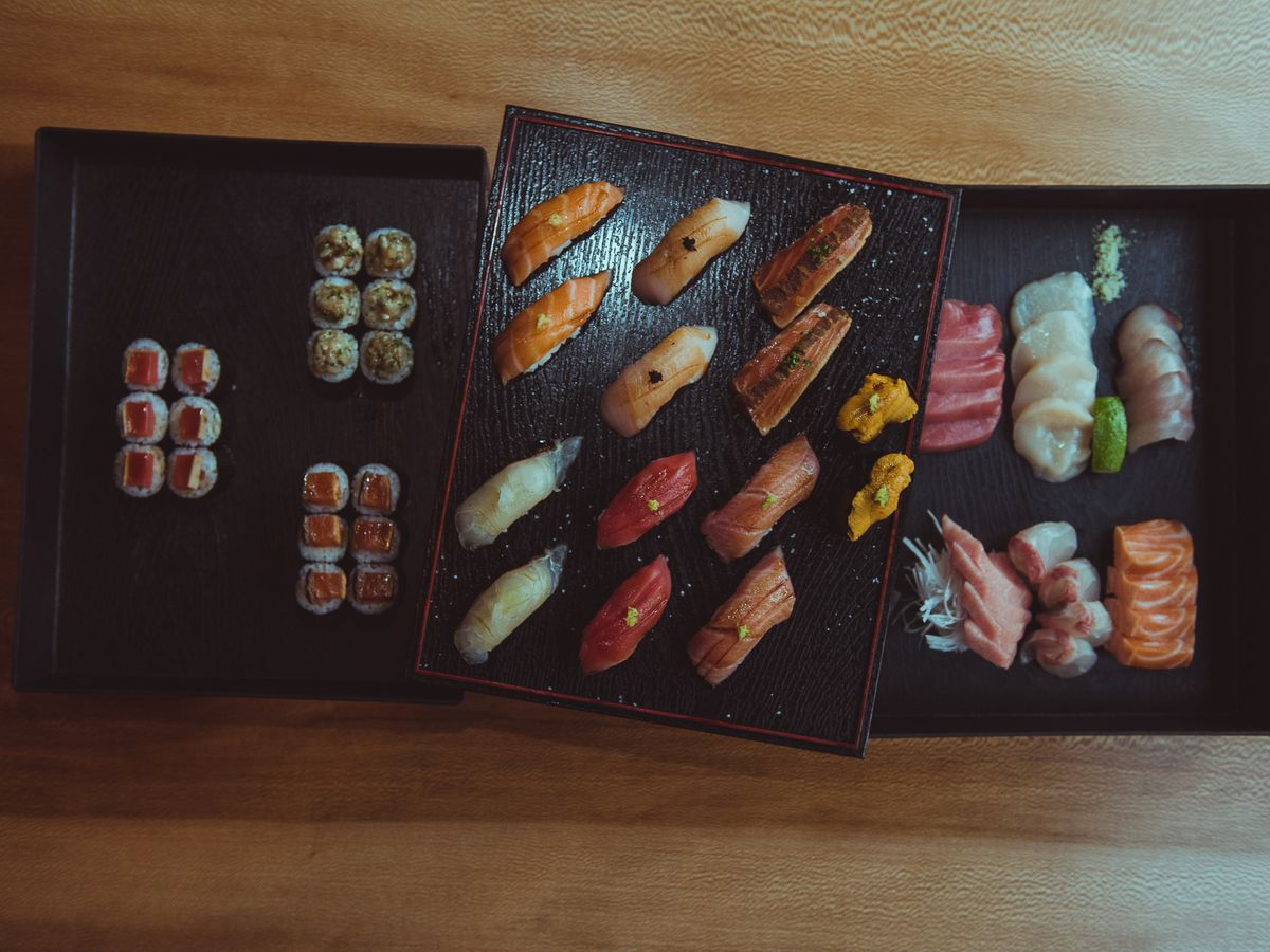 An assortment of brightly colored sushi on dark trays.