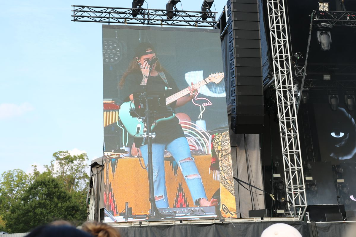 Tash Sultana plays a blue guitar and wears ripped jeans. She's seen on a massive TV next to the stage.