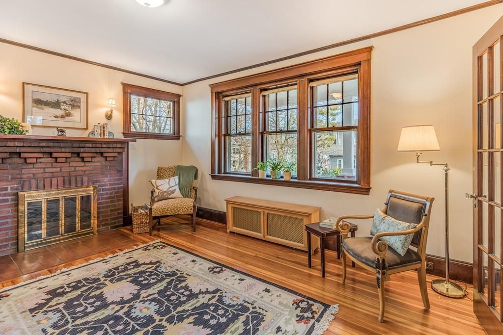 A sitting room with a large brick fireplace, some windows, and furniture.