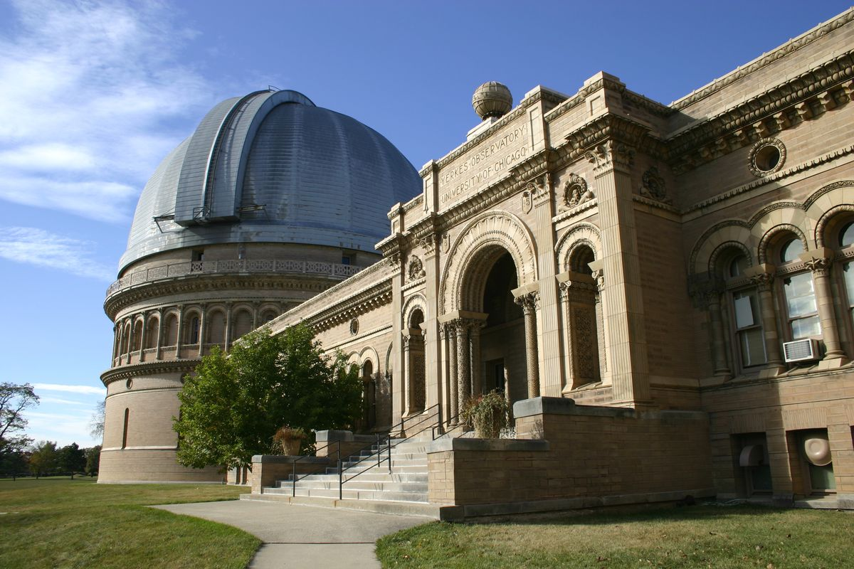 The exterior of the Yerkes Observatory in Wisconsin. There is a main building with an arched entryway attached to an observatory with a domed roof.