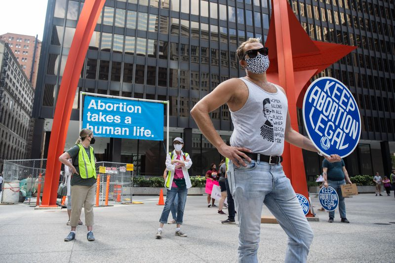 """While counter-protesters rally behind him, Jerald Kluting stands with a sign during the """"Bans Off My Body"""" protest Friday afternoon at Federal Plaza in the Loop."""