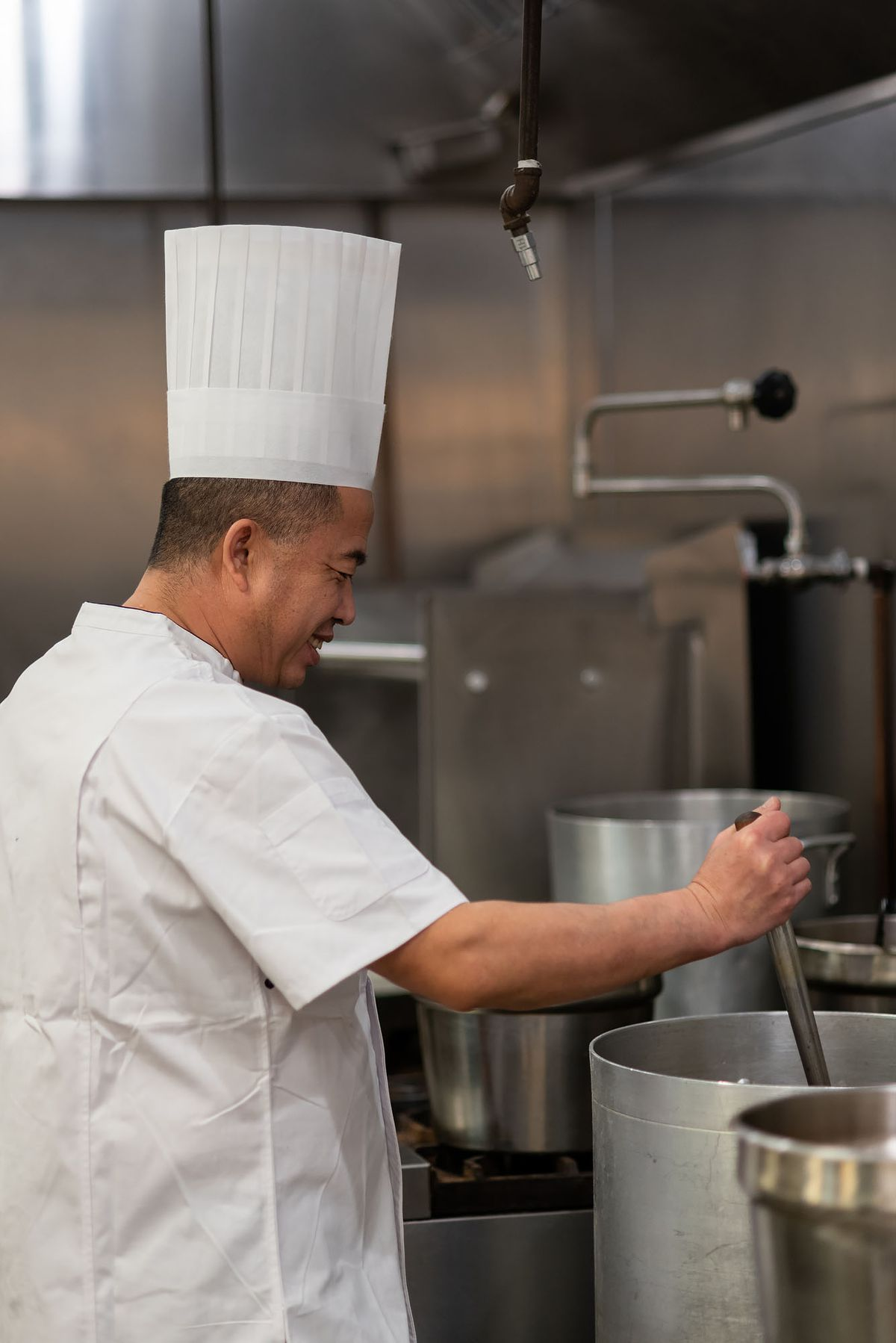 Chef making Lanzhou beef noodle soup broth.