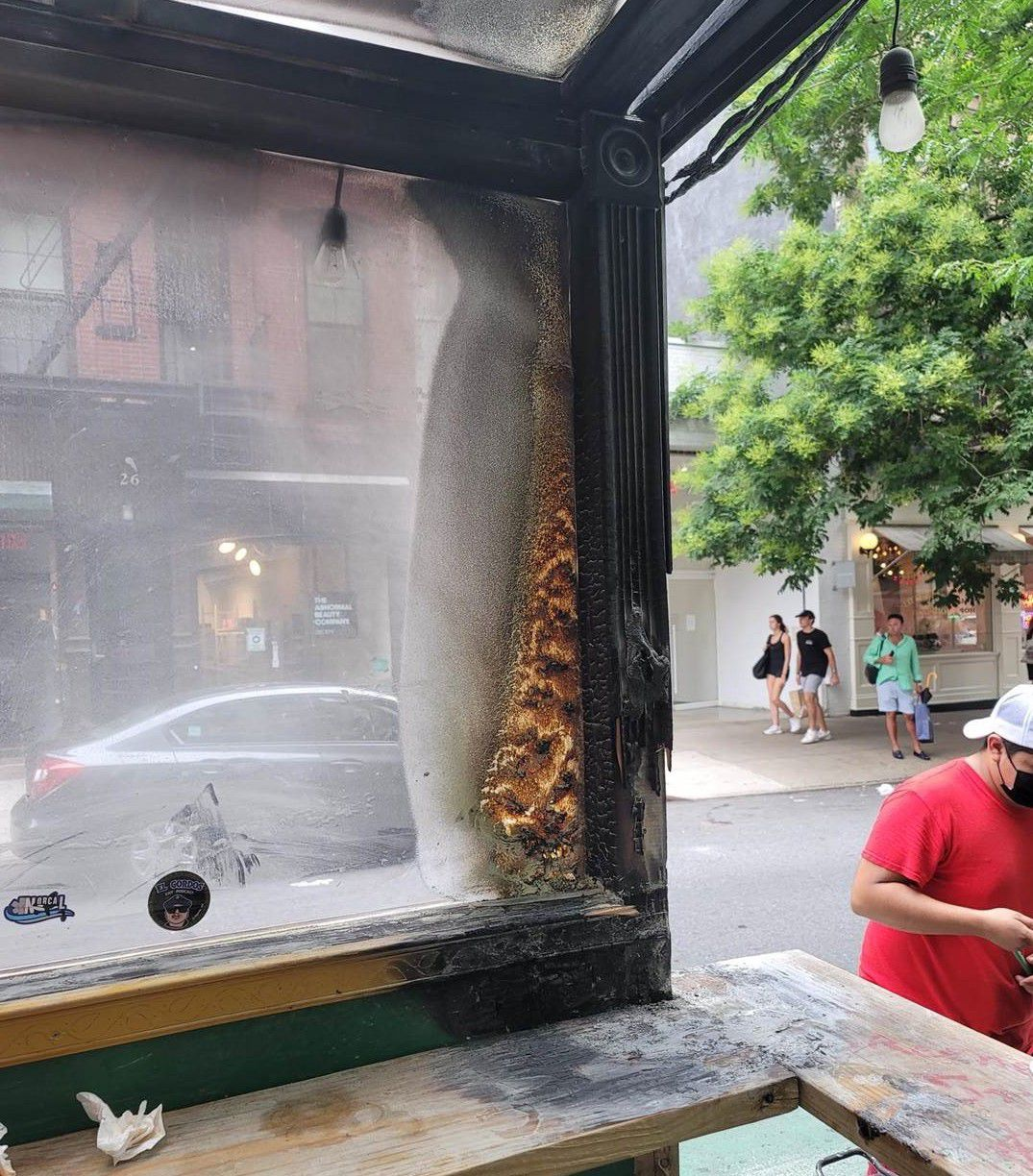A wooden outdoor dining structure is charred at one end after what appears to have been a recent fire