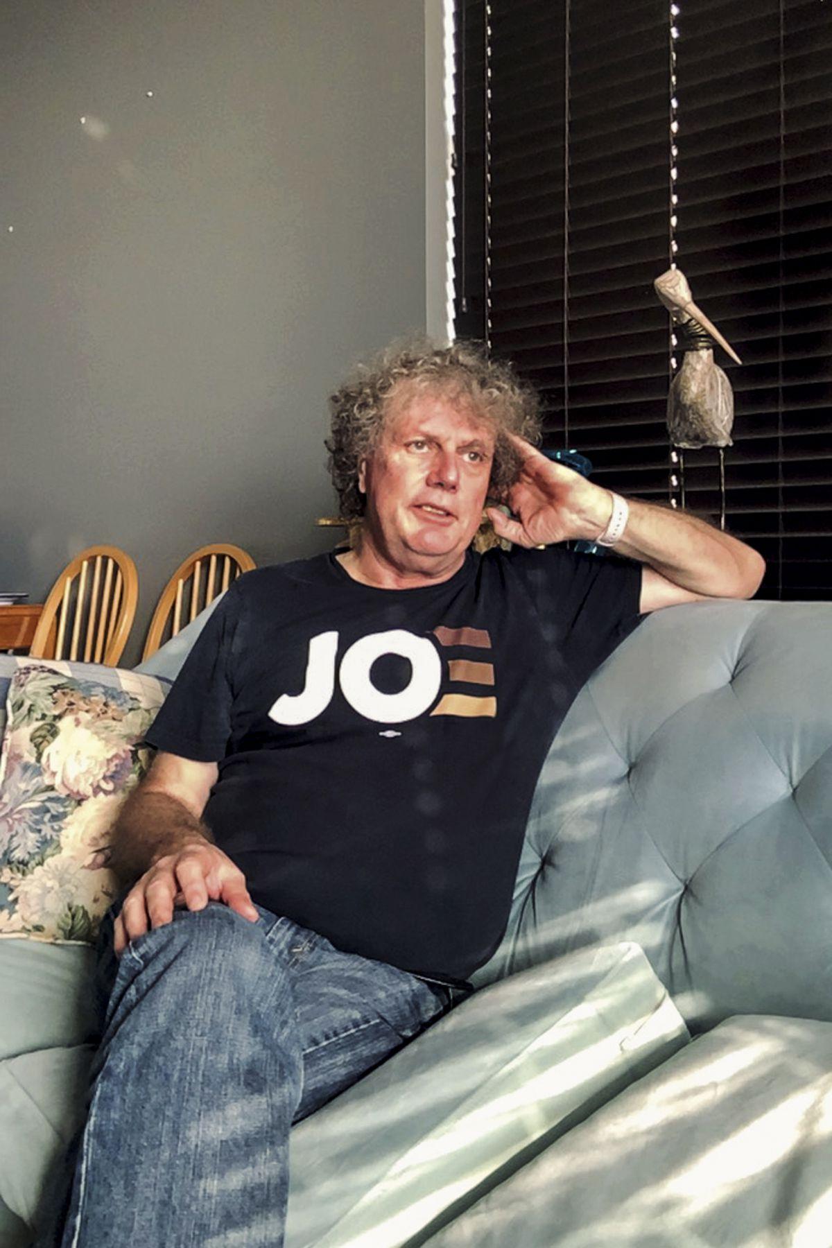 Gerard Harbison sitting in his apartment wearing a Joe [Biden] t-shirt.