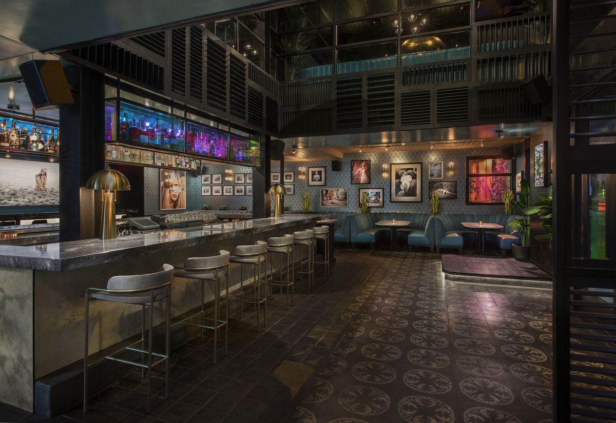 A rendering of a colorful, dim bar with marble bar and overhead booze rack.