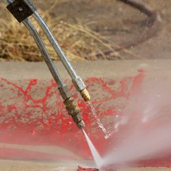 A worker with Royce Industries uses a pressure washer to remove red paint from the sidewalk at the Salt Lake County District Attorney's Office building in Salt Lake City on Friday, July 10, 2020. The building suffered tens of thousands of dollars in damage when protesters broke out at least three windows and spread red paint over large portions of the building and area in front of the structure on Thursday.