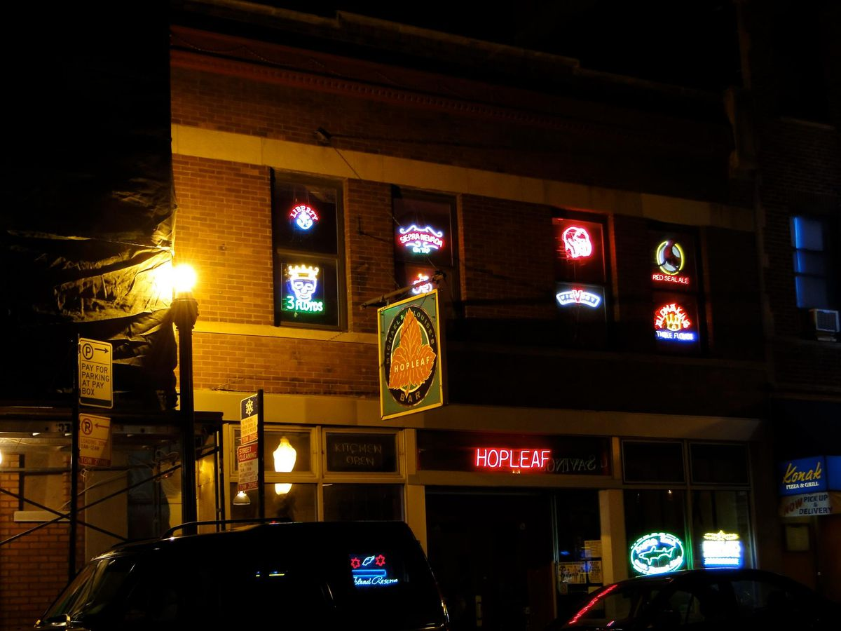 A brick building at night, lit up by neon signs