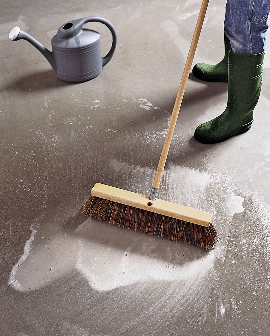 Person scrubbing the garage floor with a bristle broom.