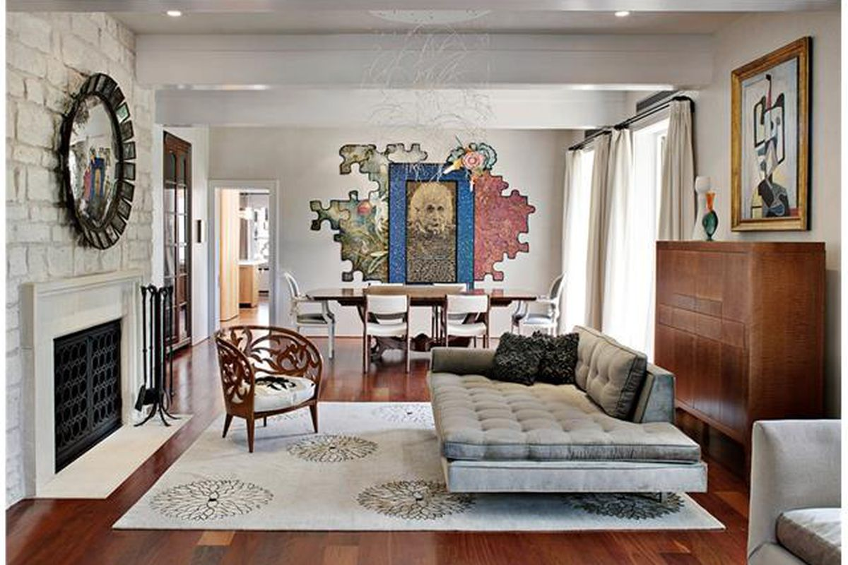Living room with white contemporary furniture, fireplace, dining table, and mural of Einstein on the wall