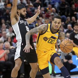 Utah Jazz guard Jordan Clarkson (00) moves around San Antonio Spurs guard Patty Mills (8) during an NBA game at Vivint Arena in Salt Lake City on Friday, Feb. 21, 2020. The Jazz lost 104-113.