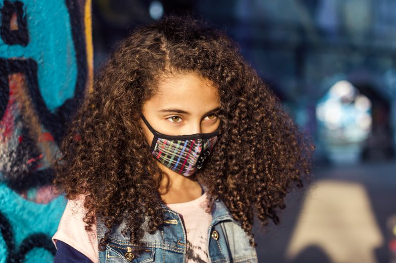 A young girl in a surgical face mask with a glitch pattern