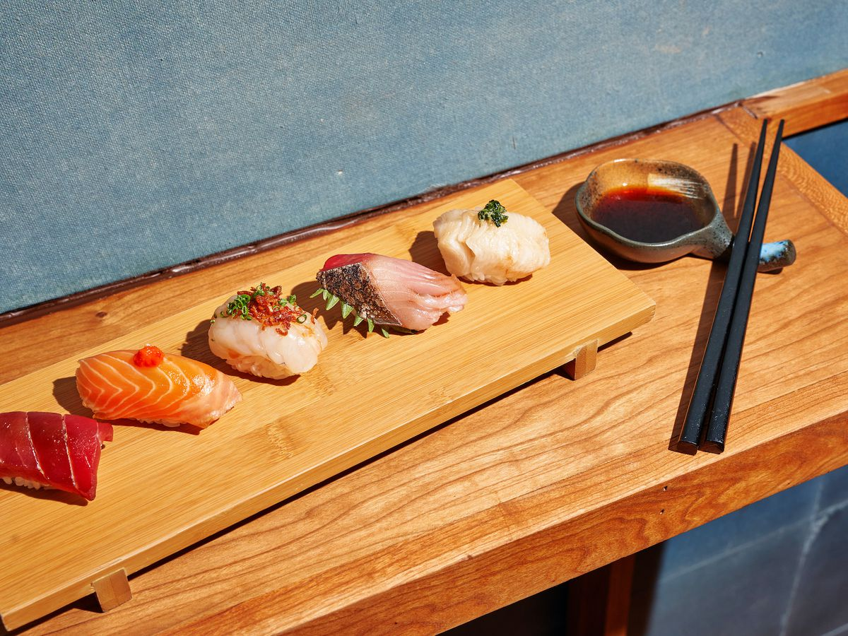 Different pieces of fish lined up on a long wooden tray with a pair of black chopsticks placed at the end