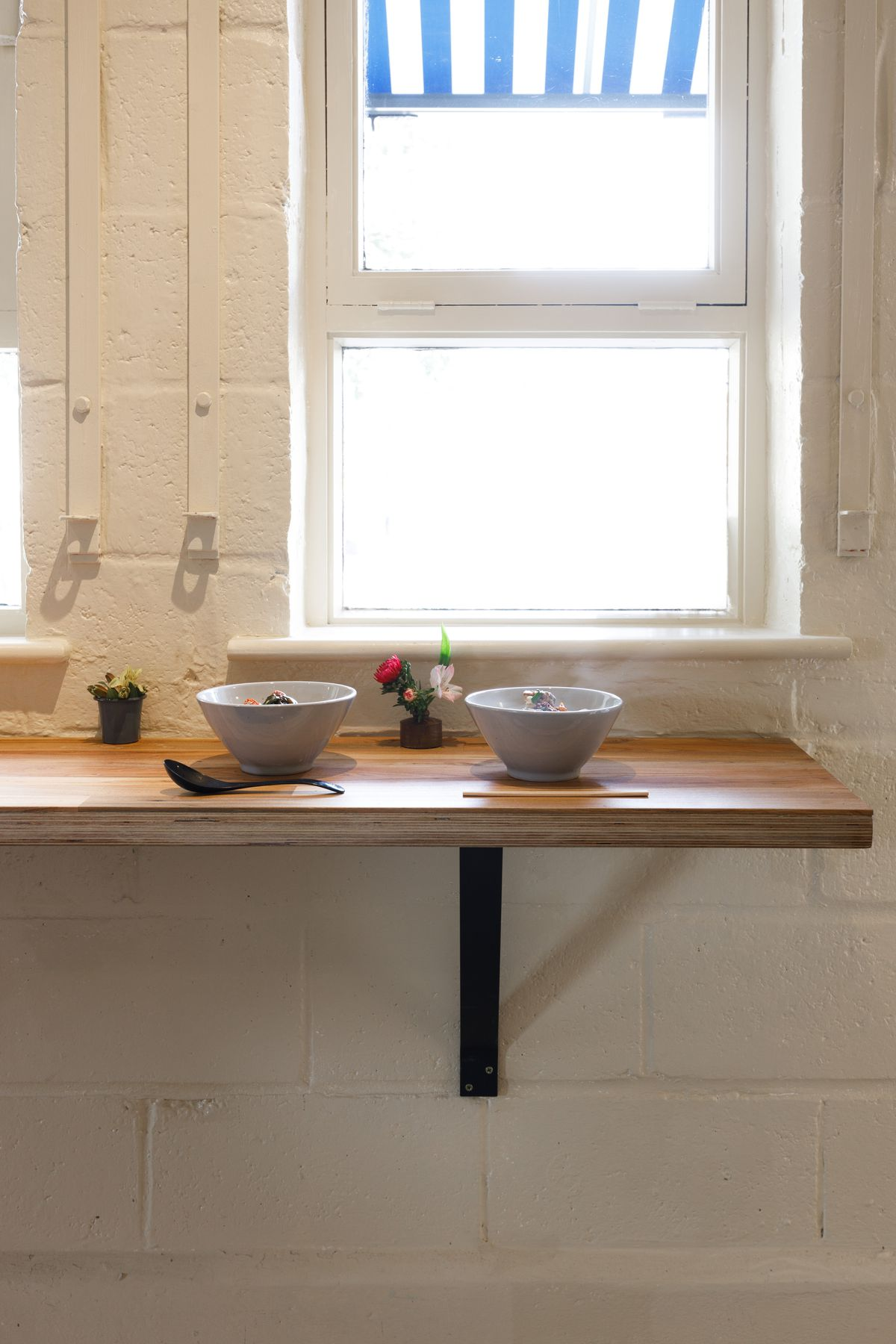 Two bowls of udon noodles on a wooden counter, secured to a white wall with a black metal bracket. Steam rises from the bowl to the right