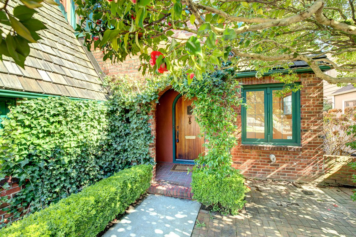 The front walkway of a brick house with green trim is covered in ivy