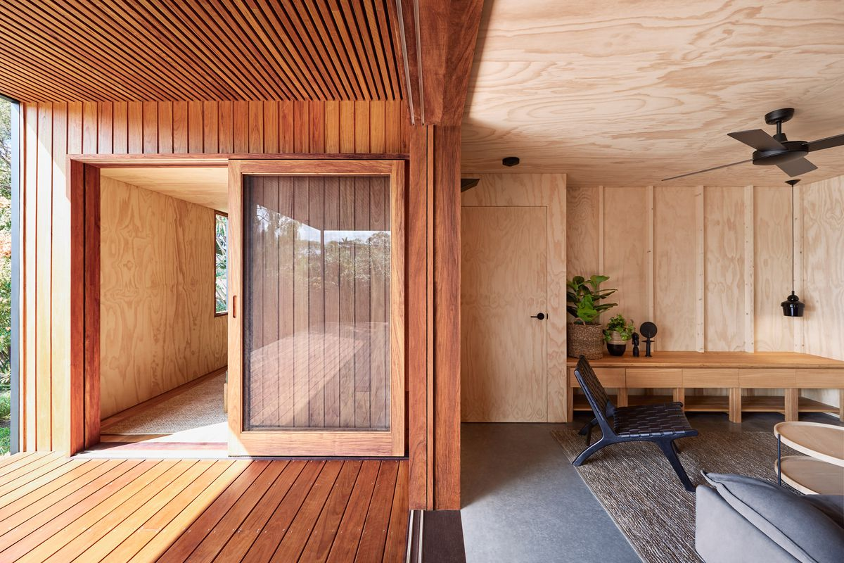 Wooden planks make up the floor, walls, and ceiling of a porch, which opens into the living room lined in plywood. The room features a black ceiling fan, black lounge chair, and tan rug.
