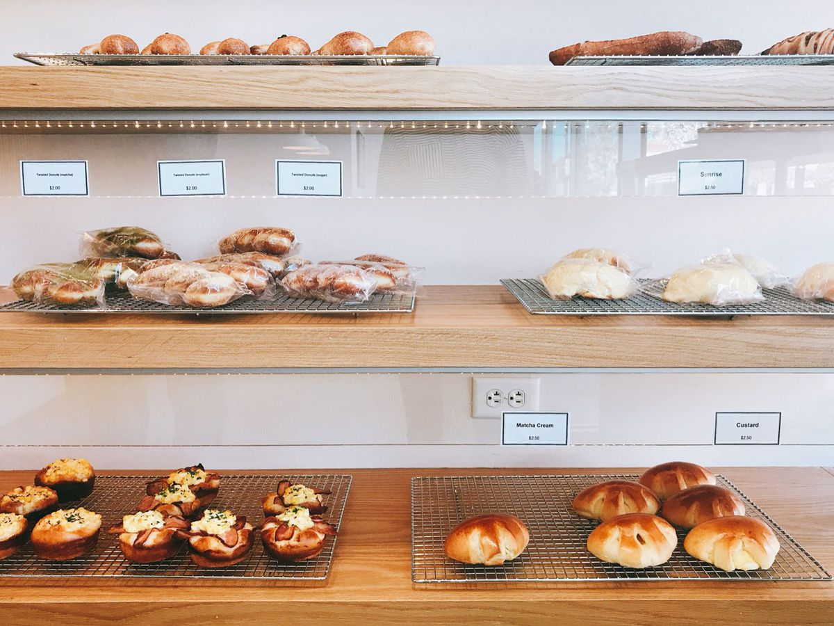 A photograph of three shelves containing selection of sweet and savory pastries at a bakery on Old South Pearl Street, including custard and matcha cream pastries.