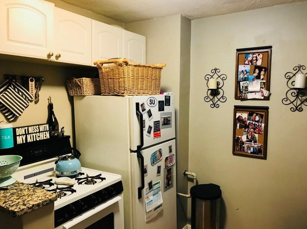 A small kitchen with the fridge in a corner next to the stove.