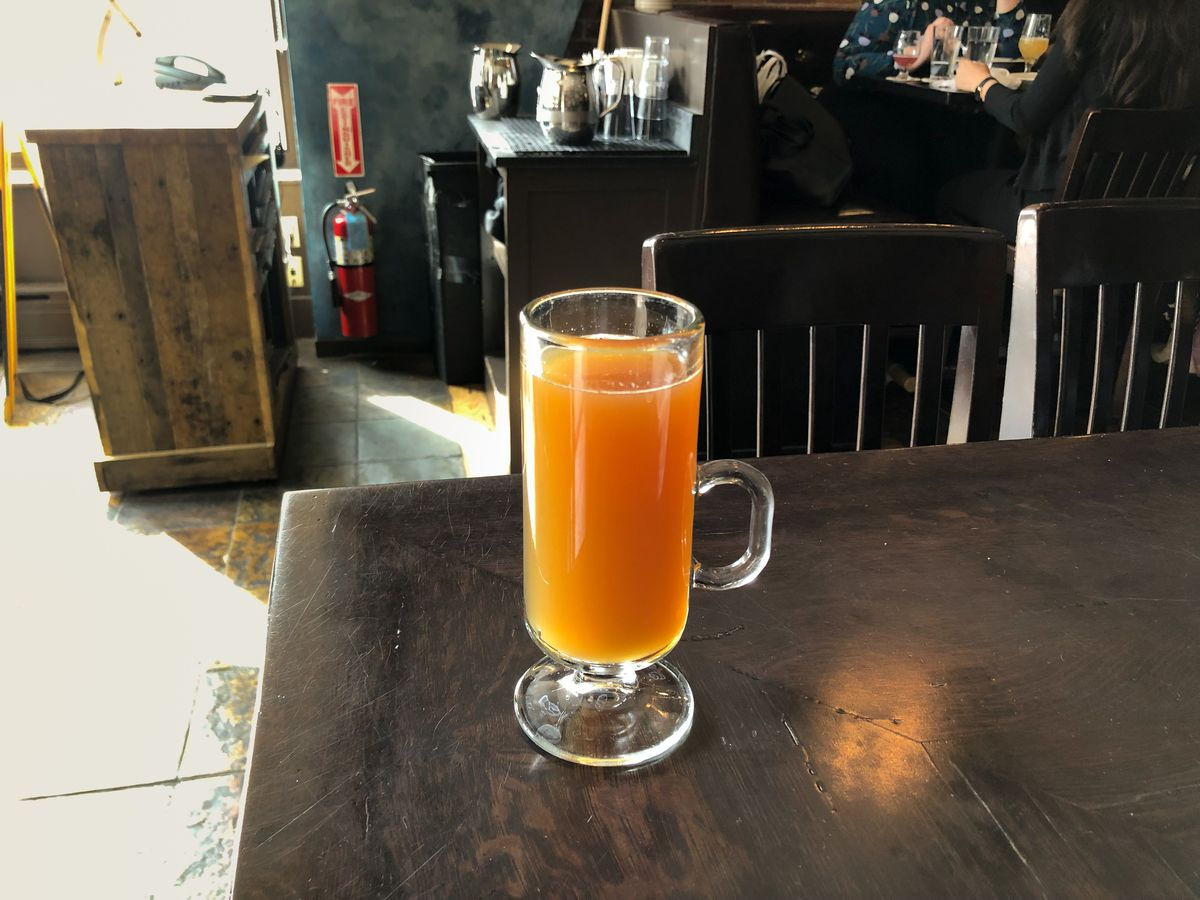 A tall clear glass mug of hot apple cider sits on a dark wooden restaurant table. Diners are visible at tables in the background.