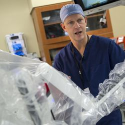 Dr. Peter Fisher explains the benefits of a daVinci Xi surgery robot at St. Mark's Hospital in Salt Lake City on Friday, Dec. 16, 2016. The robot mimics a surgeon's hand movements but with a wider range of motion using robotic arms, allowing physicians to perform complex dissections or reconstructions with a much smaller incision. As a result, patients experience less trauma, reduced pain, faster recovery times and minimal scarring.