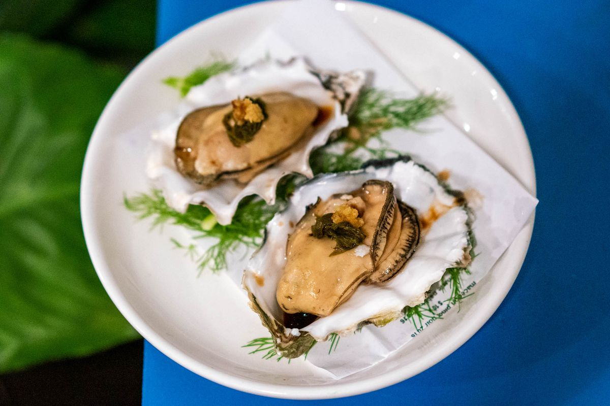 Smoked Pacific oysters on a white plate with blue in the background.