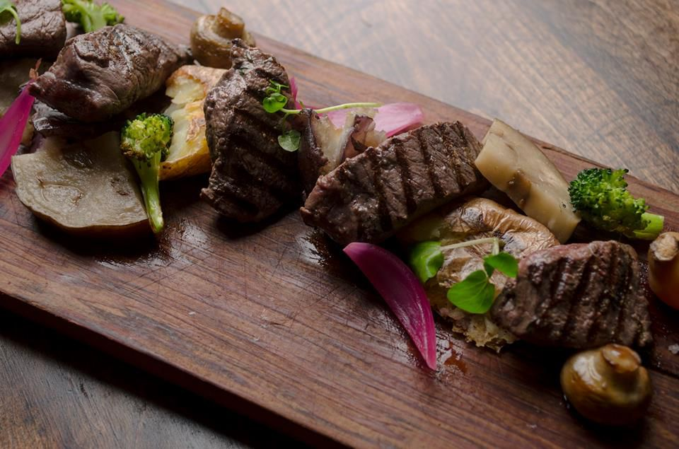 From above, a meat board with several cuts of cooked steak streaked with grill marks, mixed in with hunks of cooked vegetables and herbs for garnish
