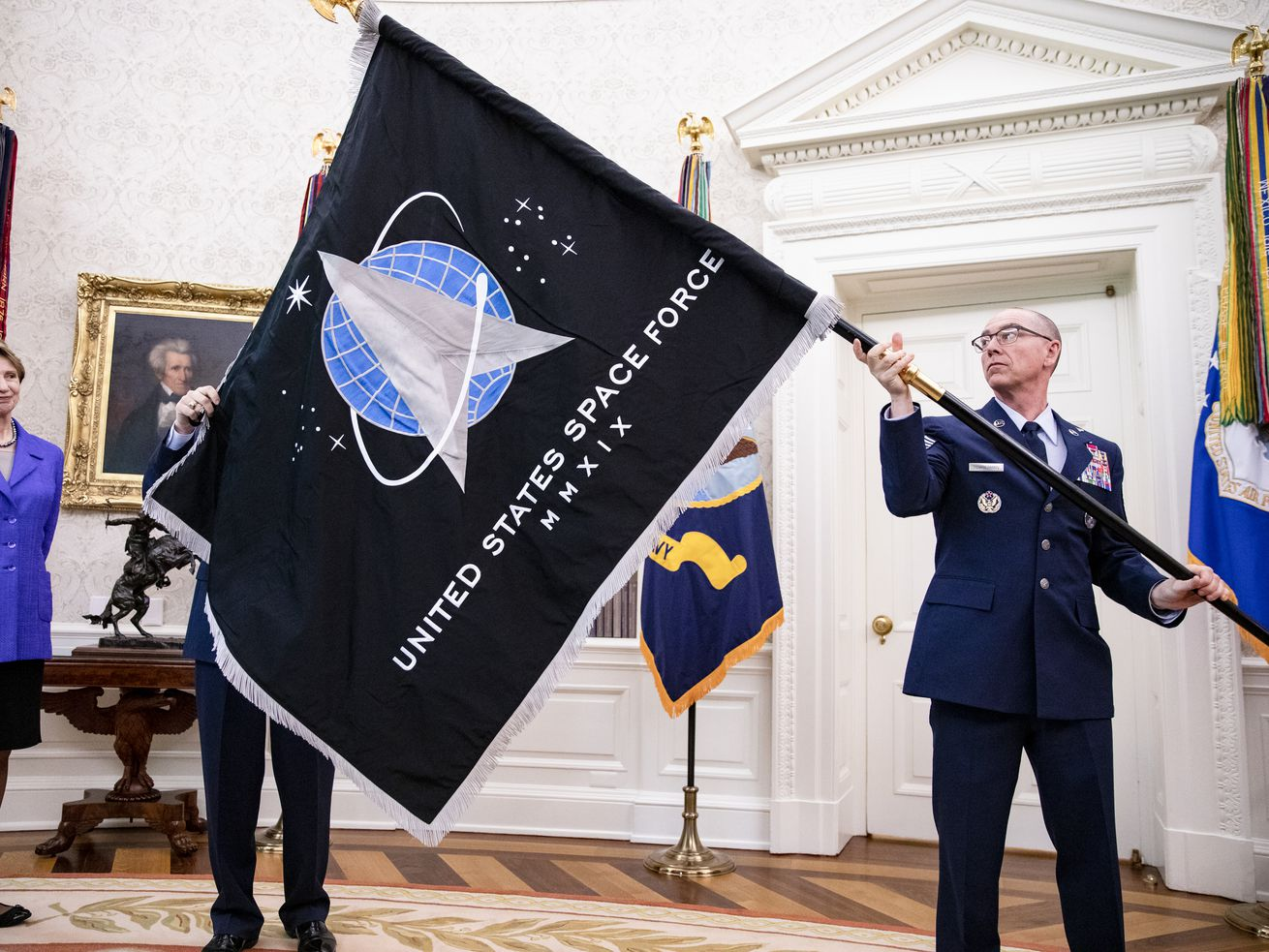 A military officer holds a US Space Force flag in the Oval Office.