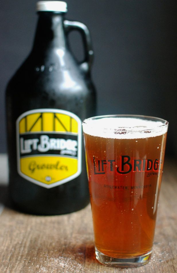 A Lift Bridge pint glass with a sugar rim full of beer in front of a growler