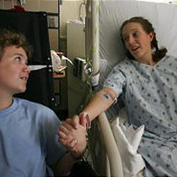 Caleb Ceran, 12, talks with sister Clarissa at University Hospital on Tuesday, which was Clarissa's 19th birthday. She was able to take two small steps.
