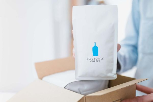 A person pulling a package of blue bottle coffee beans out of a cardboard box