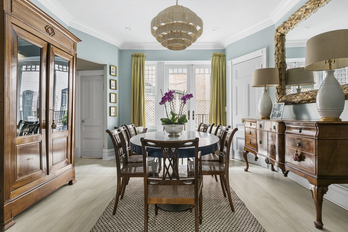 A dining area with a round table, a mirror, light blue walls, crown moldings, and wooden furniture.