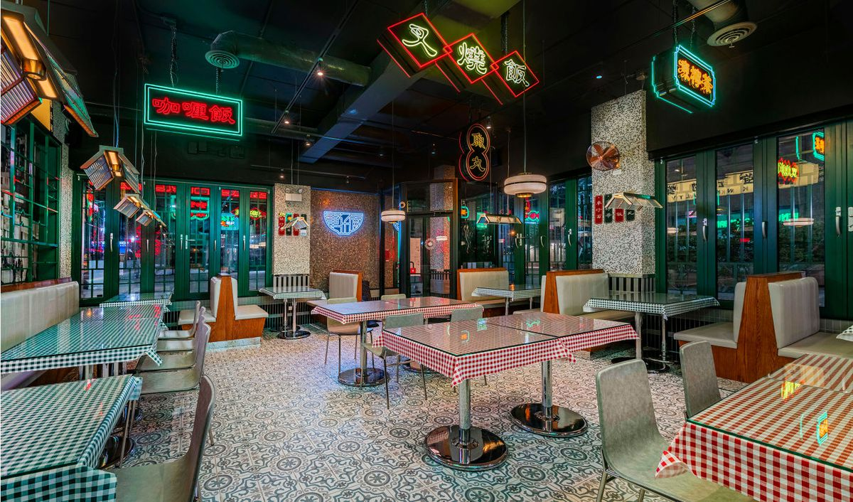A retro feel dining room with checked table clothes, booths, glass tables and neon.