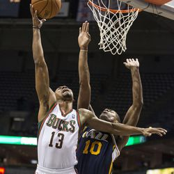 Milwaukee Bucks' Ramon Sessions, left, shoots over Utah Jazz Alec Burks during the first half of an NBA basketball game Monday, March 3, 2014, in Milwaukee. (AP Photo/Tom Lynn)