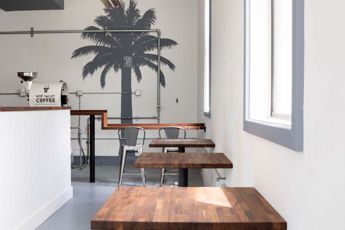 Tables, bar, and coffee roaster at Noe Cafe