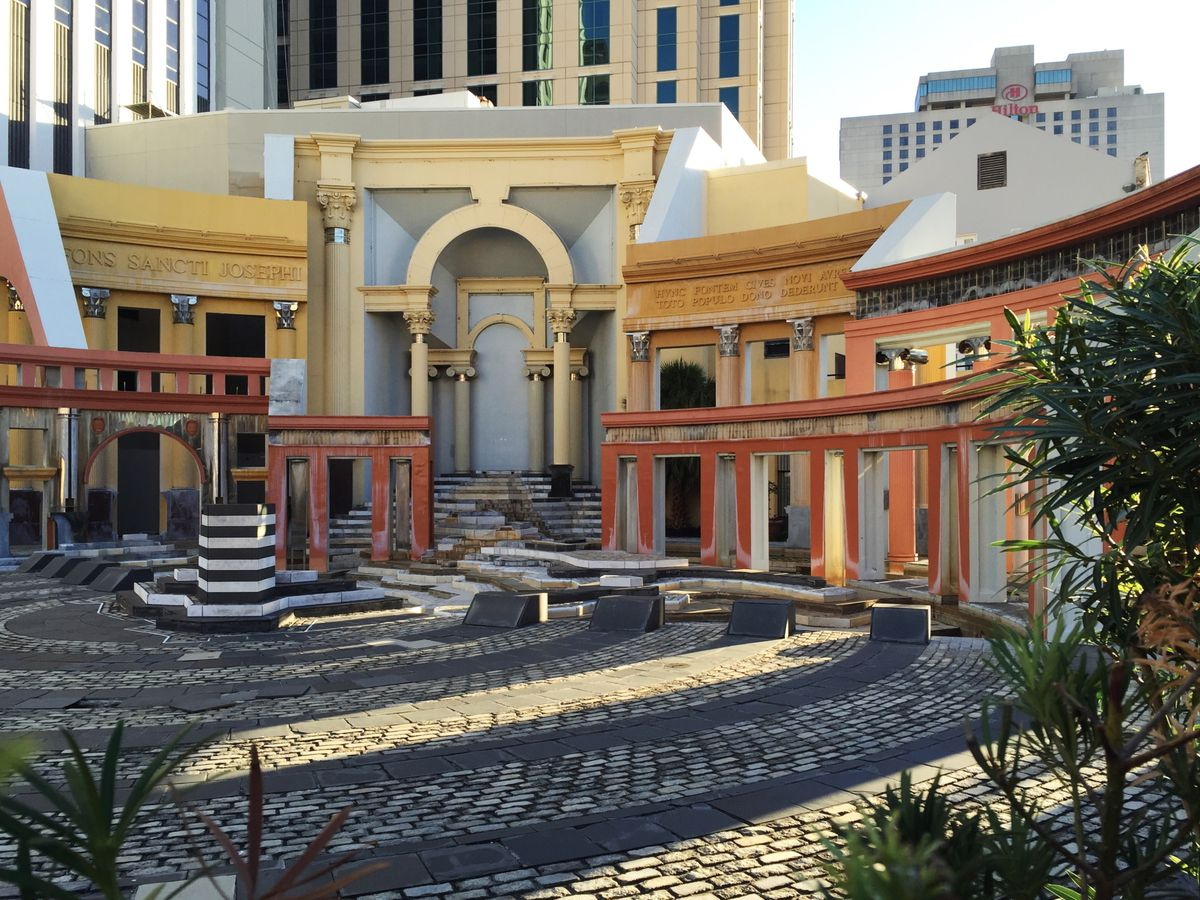 The Piazza d'Italia in New Orleans. There is a cobblestone plaza surrounded by colorful buildings.