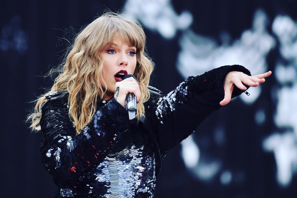 Singer Taylor Swift holds a microphone to her mouth in one hand and extends her other arm to the audience